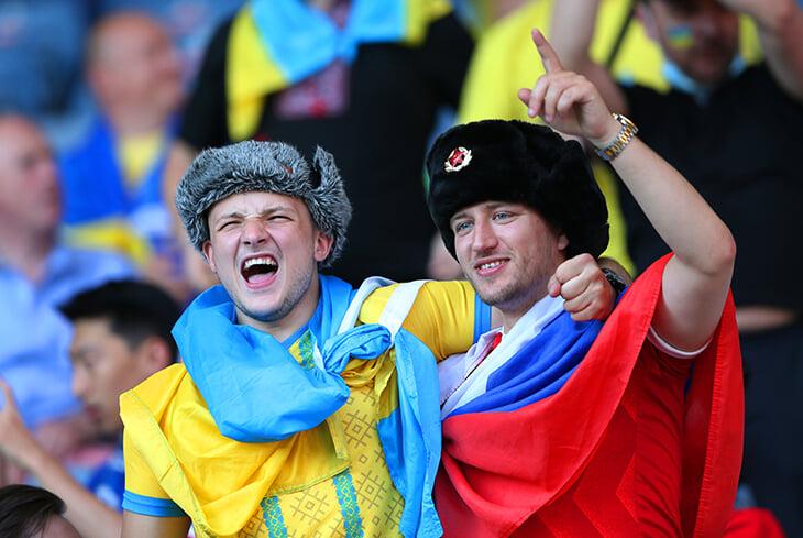 Фото дня. Двое мужчин с флагами России и Украины на матче плей-офф Евро